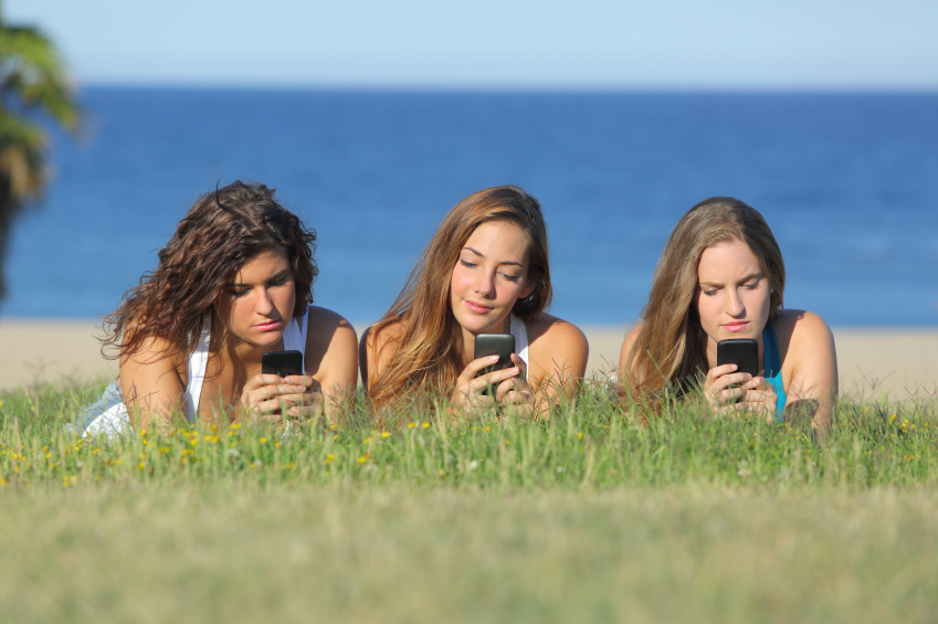 Group of three teenager girls typing on the mobile phone lying on the grass